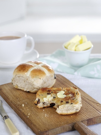 Hot cross buns with butter presented on a wooden board Stock Photo