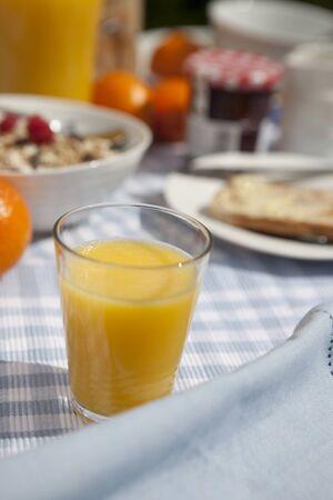 Orange juice at breakfast outside in morning sun Stock Photo