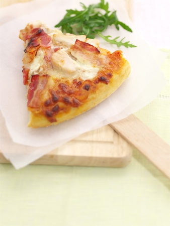 Pizza slice served on a wooden board and garnished Stock Photo