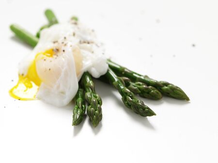 Asparagus with poached egg on isolated white background Stock Photo