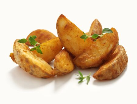 Potatoe wedges garnished with herbs on an isolated white background