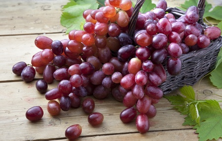 Red grapes cascading out of a wicker basket Stock Photo