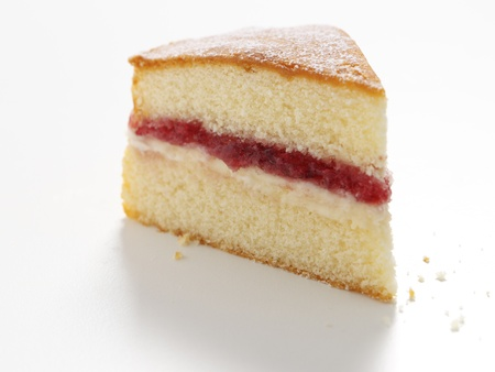 Slice of victoria sponge cake on white isolated background photo
