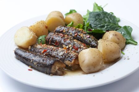Roasted Sardines garnished with chilli and garlic Stock Photo