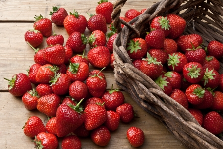 willow fruit basket: Freshly picked strawberries scattered on a rustic wooden table