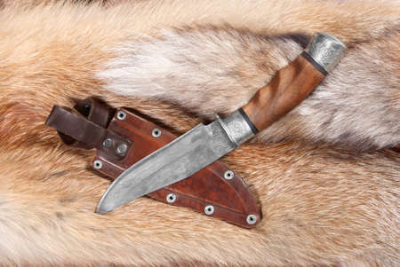 Hunting knife from braided hurlled on background of the fur Stock Photo