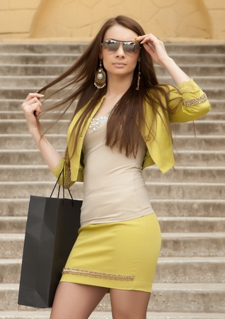 Sexy glamorous woman in sunglasses and a bag