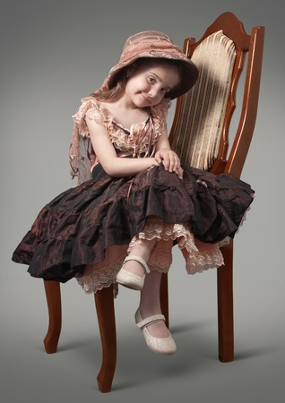 Little girl sitting on a chair a luxurious