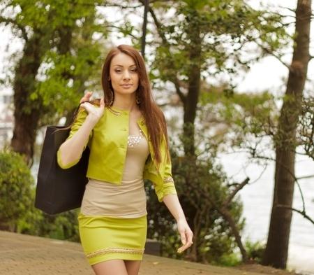 mini skirt: Sexy mujer glamorosa con una bolsa de Foto de archivo