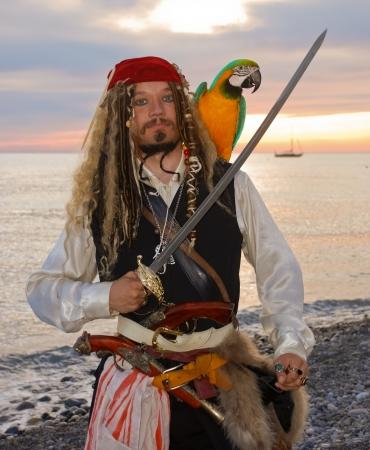 pirata: El pirata con un loro en la orilla del mar Foto de archivo