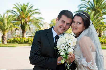 bridegroom and bride on background of the green palms Stock Photo