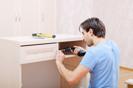 the repairer in assembly of furniture collects new furniture