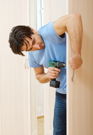door handle: man repairing the door handle furniture
