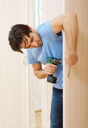 industrious: man repairing the door handle furniture