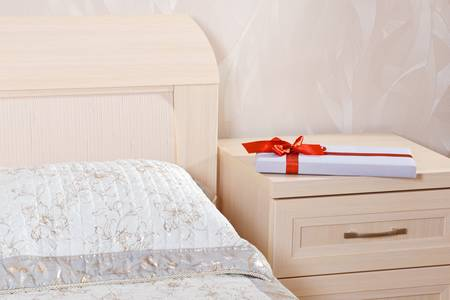 flat gift box with red bow lying on the nightstand next to the bed Stock Photo