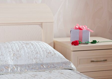 gift box with a pink tape and red rose lie on a bedside table in a bedroom
