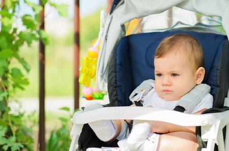 beautiful baby sitting in a pram outdoors