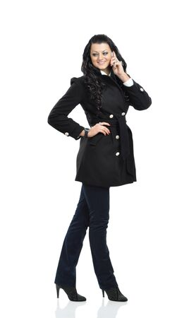 Glamorous woman in black coat speaks on a mobile phone  isolated on white