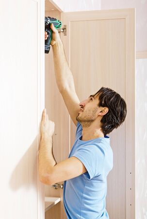 man by drill to twist screw. furniture assembly Stock Photo - 17575101