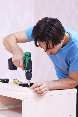 Carpenter collects wood furniture with a drill