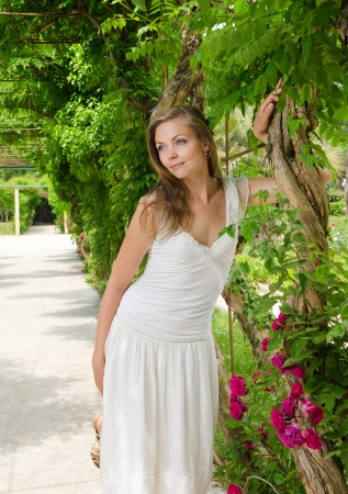 beautiful woman in white dress among the plants flower in summer  park  photo