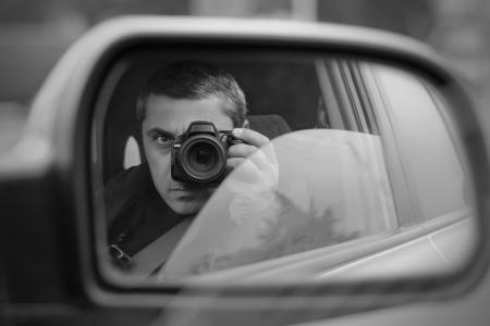 el hombre lleva a cabo lo oculto fotografiar con el coche