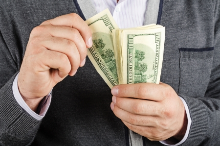 Businessman holding Cash Dollars in hands. Concept of finance success.