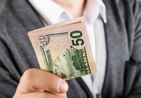 Businessman gives fifty dollars, closeup