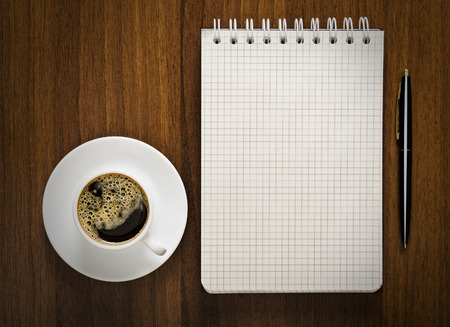 notebook with pen and cup of coffee on your desktop photo