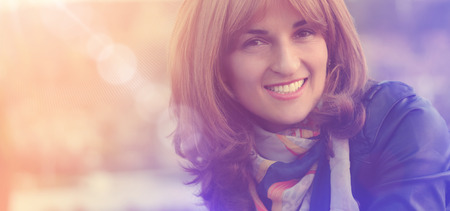 portrait of young smiling and happy woman close up, with sunlight effect photo