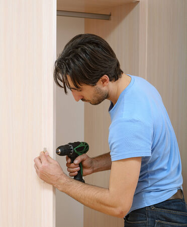 man by drill to twist screw. furniture assembly
