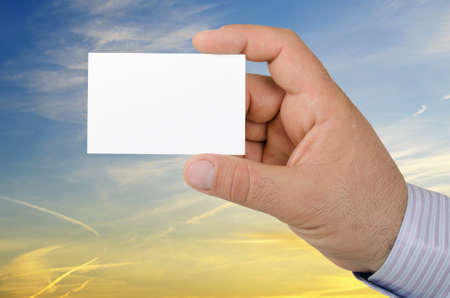 Hand holding a business card on background a beautiful sunset sky photo