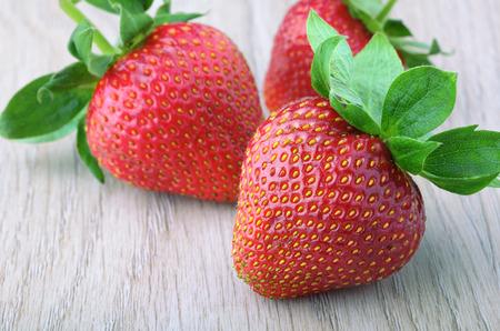 three ripe strawberries on the table closeup
