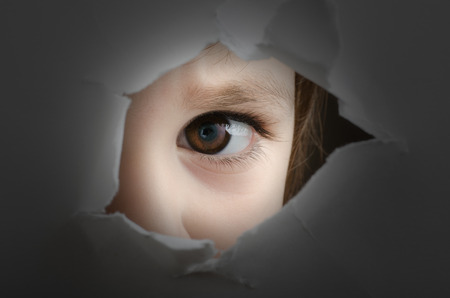 frightened child is spying through a hole in wall Stock Photo