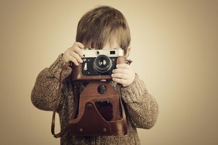 오래 된 레트로 카메라와 함께 사진을 찍고 어린 소년