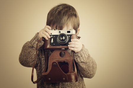 looking at camera: little boy taking pictures with old retro camera