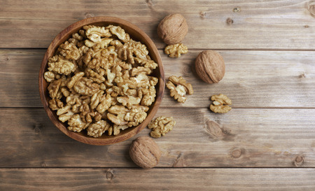 nuts: Walnuts in wooden bowl on wooden table