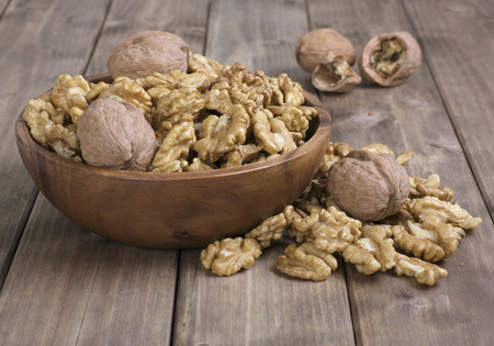 walnuts in the brown wooden bowl on table Stock Photo