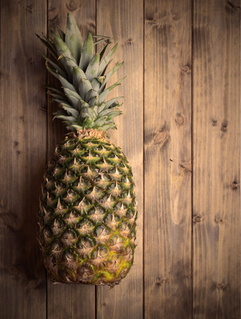 whole pineapple on a wooden table. Photo in vintage style