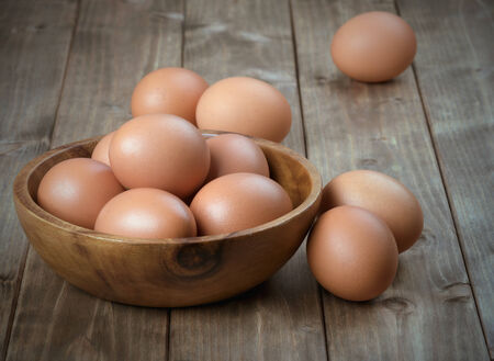 animal farm: eggs in a wooden bowl on the table from the old boards