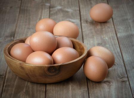 animales de granja: huevos en un cuenco de madera sobre la mesa de las viejas tablas