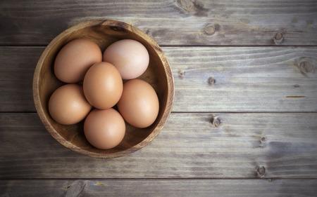 huevo: huevos en un cuenco de madera sobre la mesa de las viejas tablas