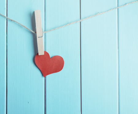 red heart made of paper with clothespin hanging on a rope and wooden blue  planks background with space for text