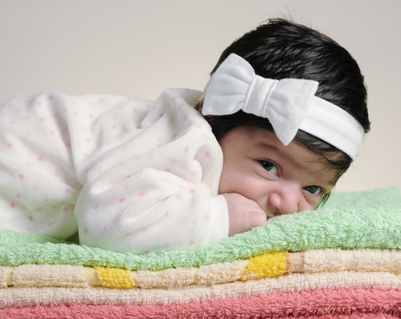 0 6 months: baby lying on a towel looking at the camera Stock Photo