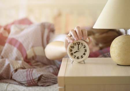 clock: girl turns off the alarm clock waking up in the morning from a call