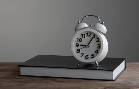 closed book: Alarm clock standing on of closed book Stock Photo