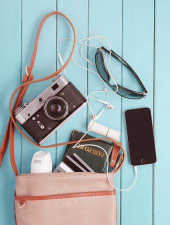 女性のバッグ、さまざまな個人の持ち物とレトロなカメラです。セットの旅行者