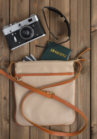 stuff: female bag with retro camera passport and credit cards on a wooden table.