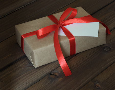 Vintage gift box wrapped in kraft paper and red ribbon on wooden background Stock Photo