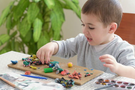 sculpting: Little boy playing with clay, sculpting figures.